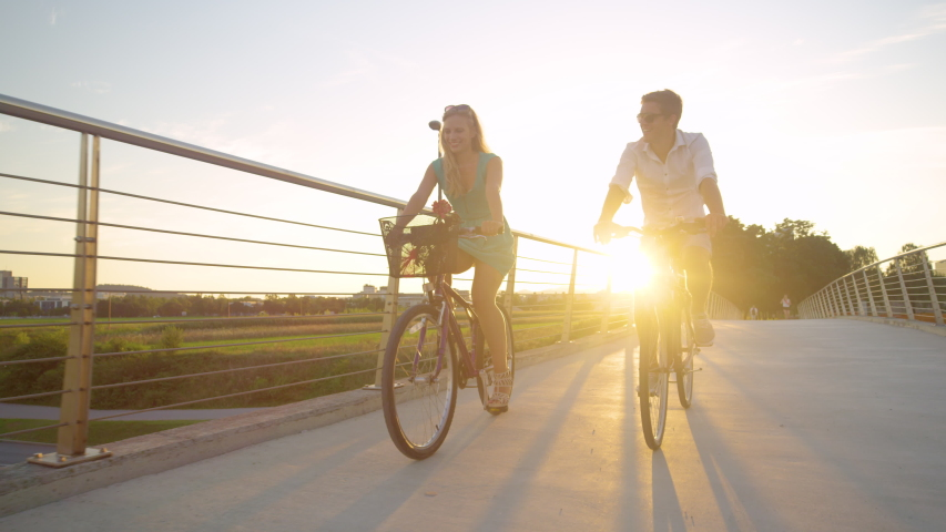 SLOW MOTION, LENS FLARE, LOW ANGLE: Young woman smiles while riding her bike with her boyfriend at sunset. Cinematic shot of an adorable young couple enjoying a sunny evening by riding bicycles. Royalty-Free Stock Footage #1047721513