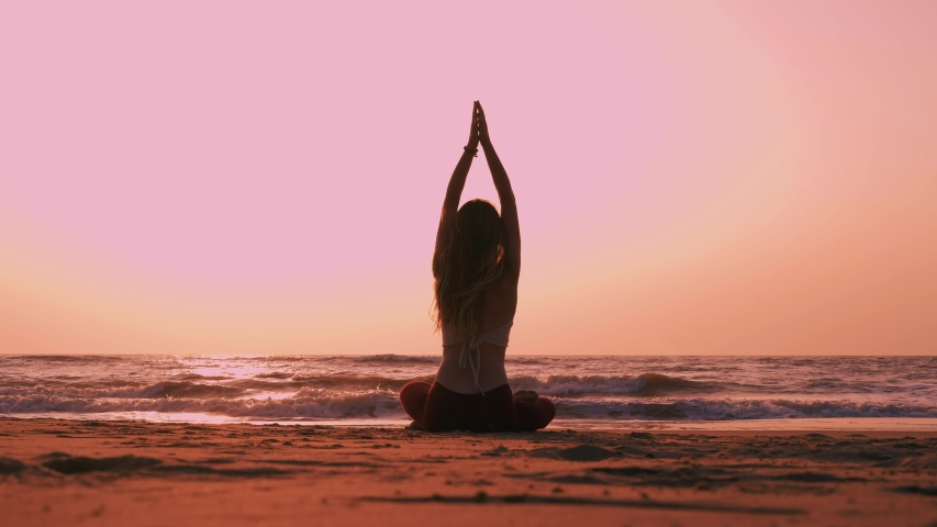 Beautiful free and wild woman sitting in meditation pose on the Indian beach lotus position medicine yoga asana balance kundalini energy every day routine practice good for woman health mindfulness