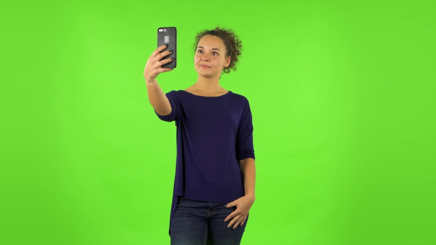 Curly woman making selfie on mobile phone then looking photos . Green screen | Shutterstock HD Video #1047747229