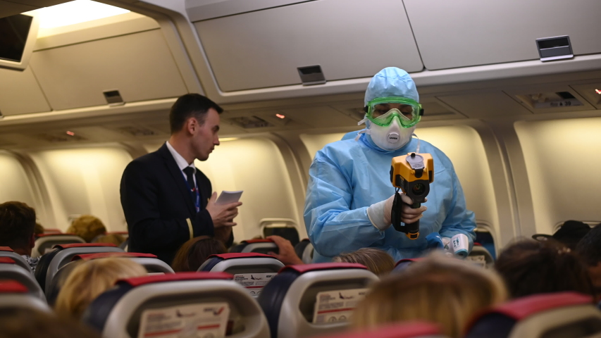 Moscow - March 04 2020. Temperature check on a corona virus at airplane. Medical official wearing infectious disease protection suite measure temperature of passengers inside the aircraft on arrival.