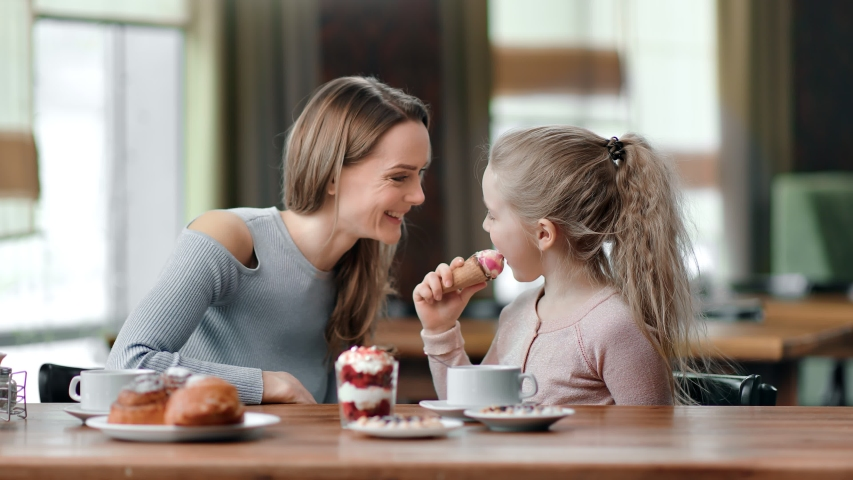 Happy mother and daughter eat dessert and drink tea together at cafe having fun. Playful kid girl licking ice cream smearing to mom nose laughing have positive emotion. Medium shot on RED camera | Shutterstock HD Video #1047752101