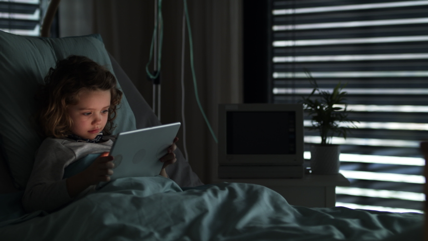 Bored small girl in bed in hospital, using tablet to pass time.   Shutterstock HD Video #1047755791