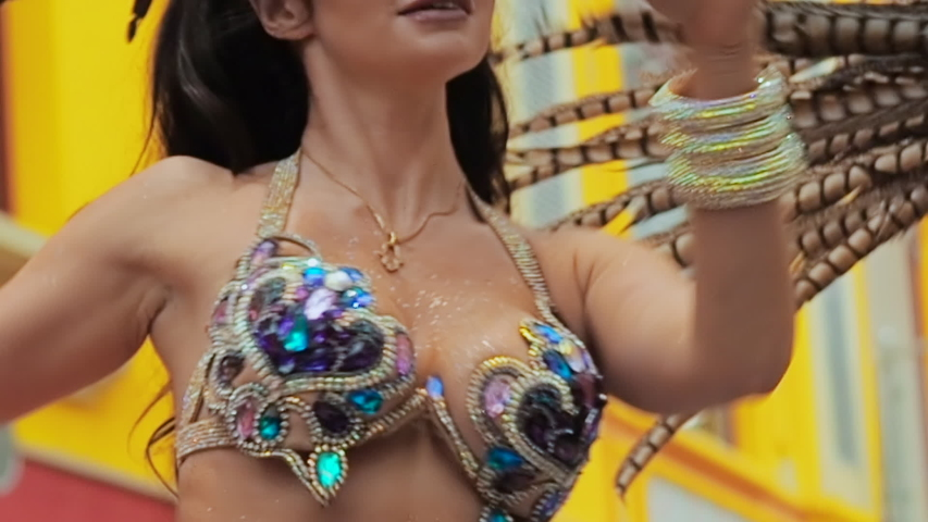 The celebration of the Brazilian carnival in Moscow. Beautiful girl bright colorful carnival costume decorated with rhinestones dancing samba against the background of a yellow building. Half-naked | Shutterstock HD Video #1047759211
