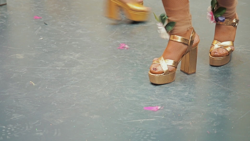 The celebration of the Brazilian carnival in Moscow. Female legs in golden sandals dance a Brazilian samba. Women's feet in shoes with heels. Dancer legs heeled sandals on dance floor | Shutterstock HD Video #1047759229