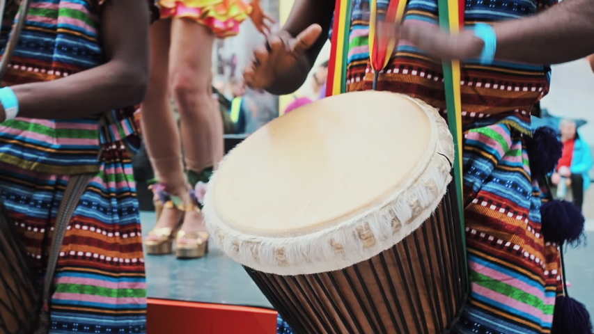 The celebration of the Brazilian carnival in Moscow. Musician beats rhythm on african drums. Black artists hit the drums with their hands. Girls dancers dance samba. Close-up African s hands playing | Shutterstock HD Video #1047759241