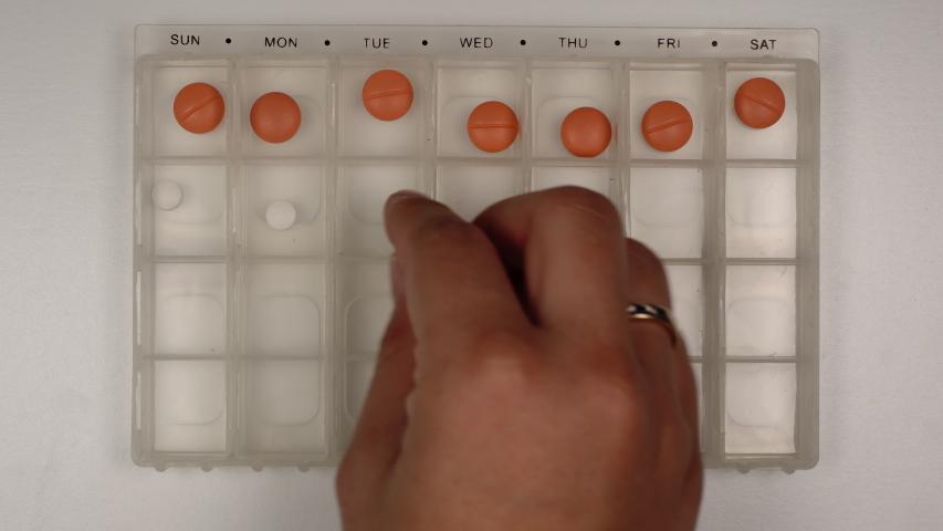 Female hand puts down a pills into a pill organizer, Top view