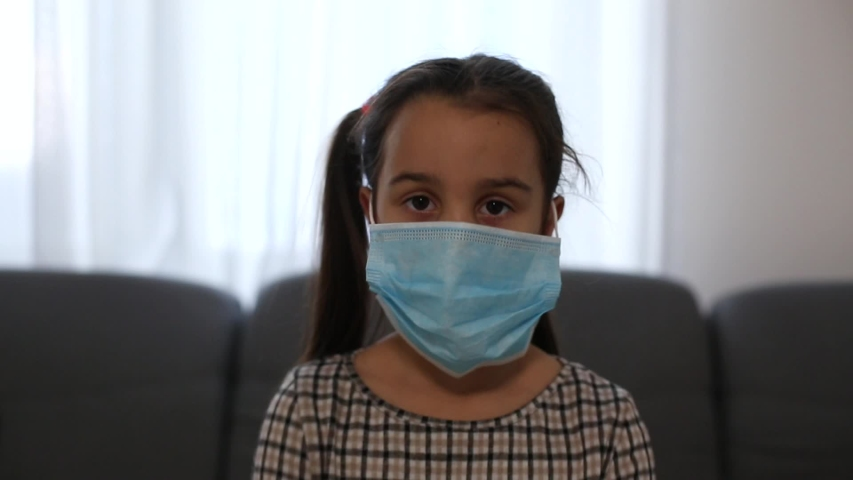 Sick little girl wearing a medical mask against virus closeup lokking at camera - Concept of coronavirus protection | Shutterstock HD Video #1047765628