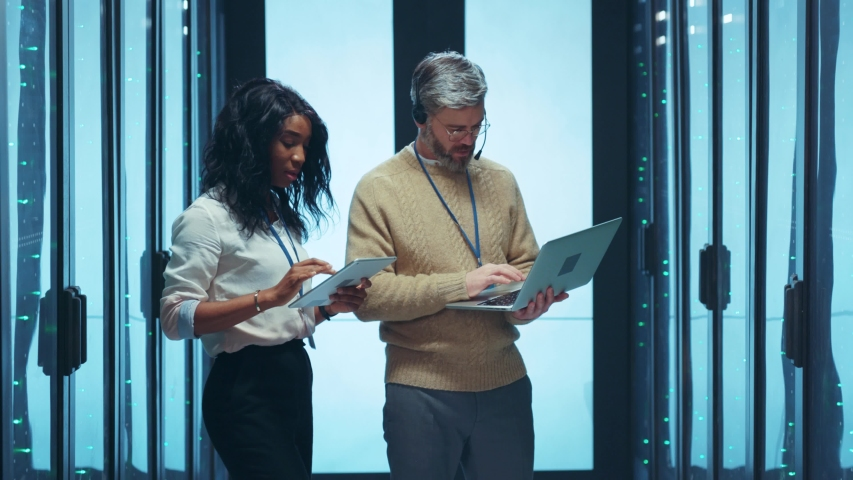 Interracial IT couple of engineers performing network management operations in server room discussing plans working together at data center storage. Teamwork. Royalty-Free Stock Footage #1047769903