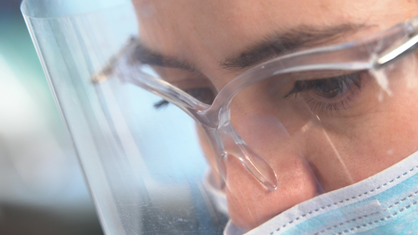 Close-up of a female doctor's eyes through a protective mask and medical glasses during work.