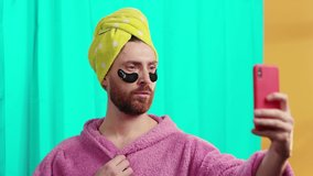 Happy sexy transgender guy in bathrobe and eye patches throwing air kisses on smartphone video call talk with boyfriend posing in the bathroom. Comedy concept.