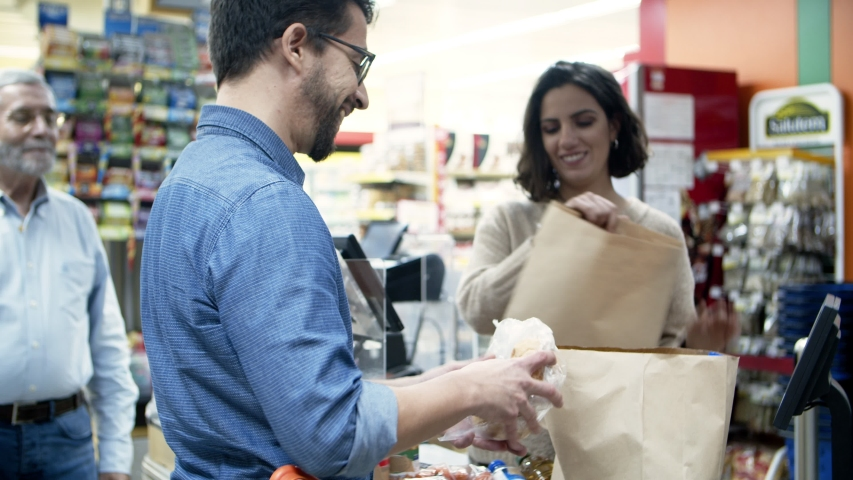 Man and woman packing goods into paper bags. Smiling young man and woman packing products into shopping bags in grocery store. Supermarket concept