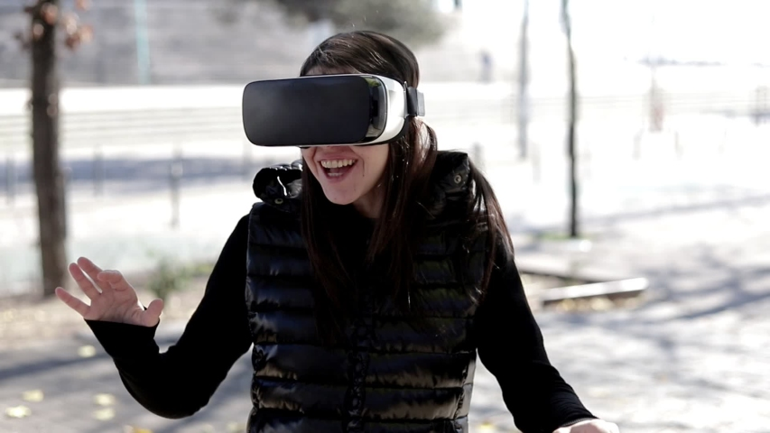 Happy woman in VR headset on street. Handheld shot of cheerful young woman using virtual reality headset outdoors. Wearable technology concept #1047780247