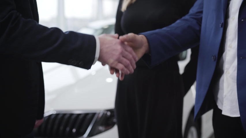 Handshake of unrecognizable men in car dealership. Caucasian trader shaking hand of Middle Eastern client in showroom. Auto industry, business, success, lifestyle. | Shutterstock HD Video #1047781558