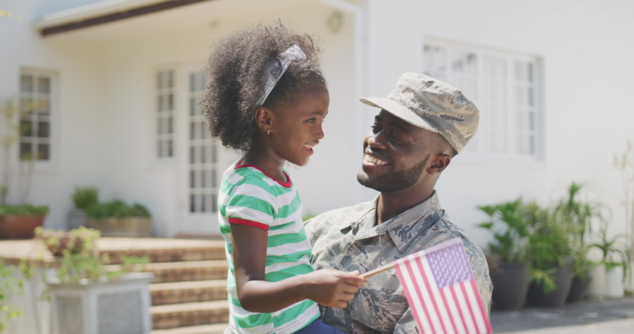 Front view of a happy African American man enjoying time in the garden, with his family, wearing military uniform, holding up his African American daughter holding a flag, on a sunny day