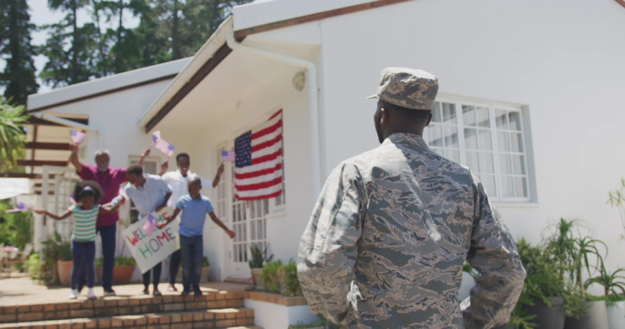 Rear view of an African American man enjoying time in the garden, with his family, wearing military uniform, returning home, with his multi-generation family greeting him, with his children running