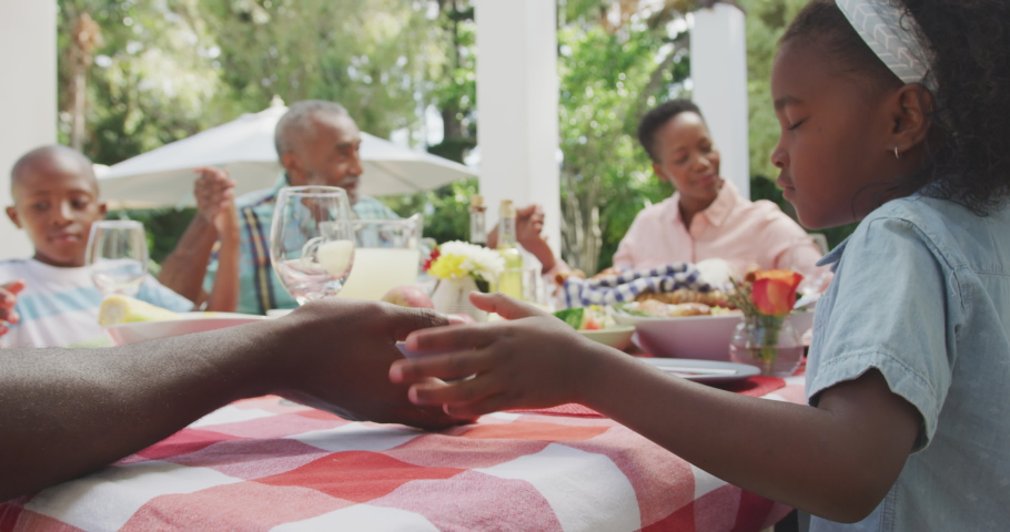 Side view of a multi-generation multi-ethnic family having a good time in a garden, sitting by a table with food on it, holding hands, saying grace on a sunny day, in slow motion