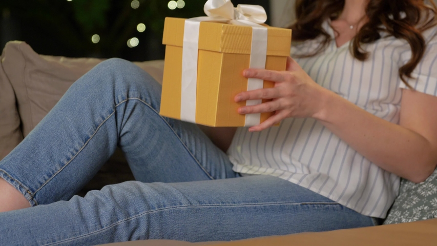 Pregnancy and people concept - happy smiling pregnant woman with gift box on sofa at home