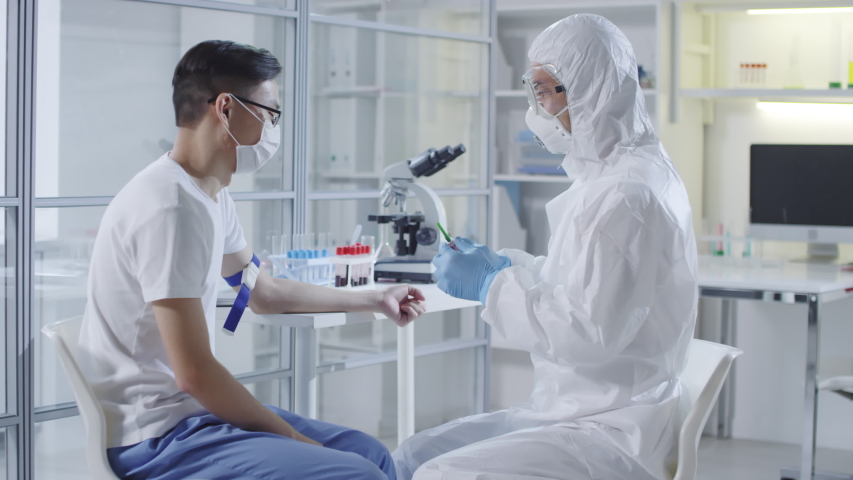 Tracking of unrecognizable doctor or medical scientist in protective suit, gloves, mask and goggles injecting sick Asian patient with experimental vaccine from coronavirus | Shutterstock HD Video #1047813007