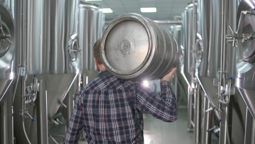 A working male brewer carries a keg filled with beer as he passes beer tanks. close-up. back view   Shutterstock HD Video #1047821836
