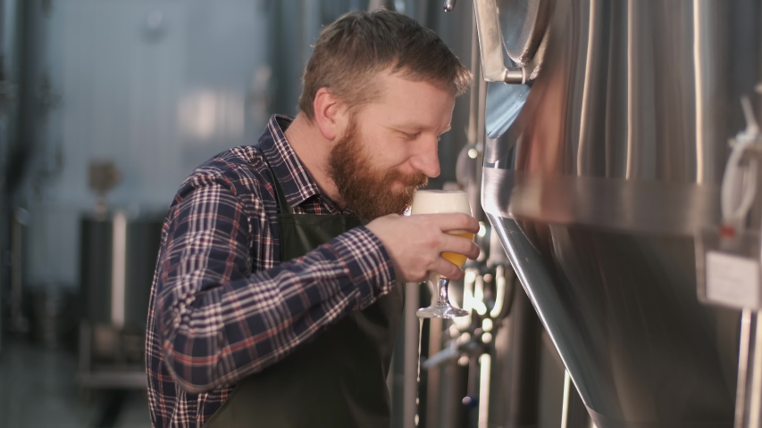 A male brewer pours freshly brewed beer from a beer tank and tastes it while enjoying its smell. | Shutterstock HD Video #1047821923