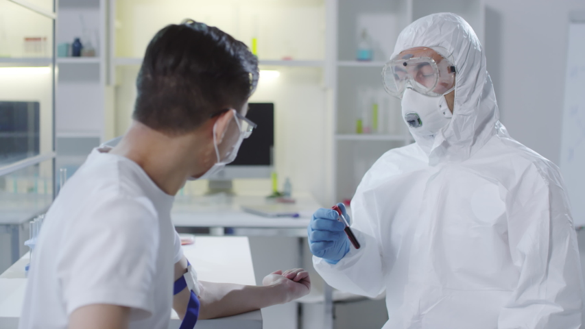 Medium shot of unrecognizable doctor in disposable coveralls, goggles, respiratory mask and gloves holding tube with blood sample and explaining something to sick patient | Shutterstock HD Video #1047823612