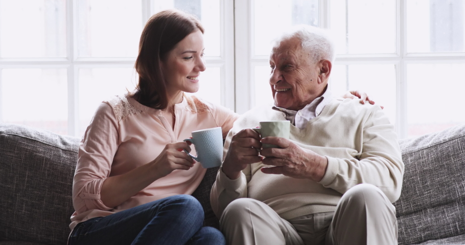 Happy senior elder father grandfather and young adult granddaughter grown daughter talking bonding drink tea sit on sofa, loving 2 two generations family embracing enjoy friendly conversation at home