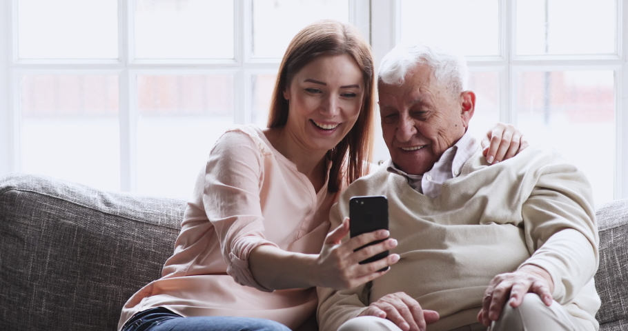 Cheerful young adult grownup granddaughter laughing watching funny social media videos using smart phone sit on sofa embracing teaching elder grandpa older generation having fun relaxing with gadget