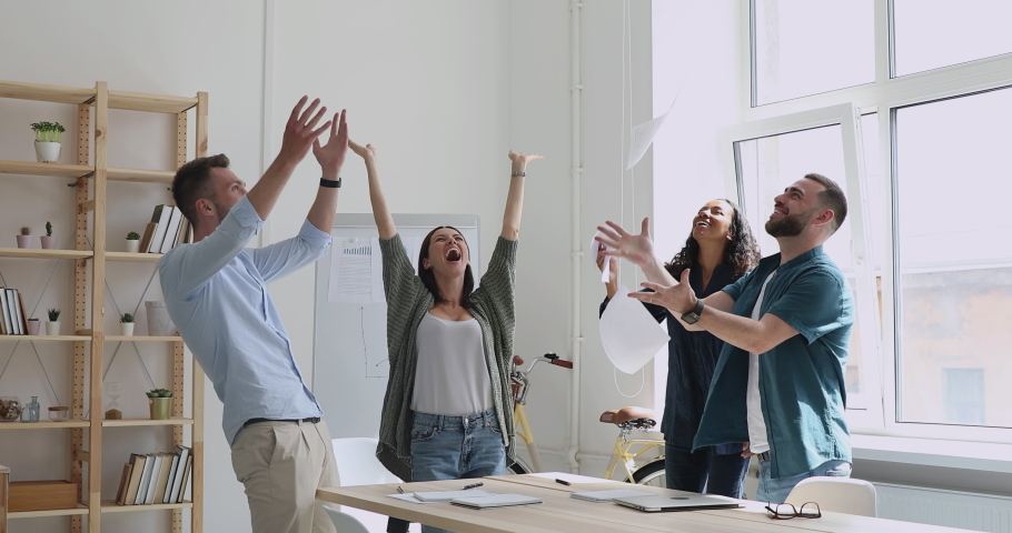 Overjoyed young multiracial team holding papers in hands, celebrating corporate success together in workplace. Excited mixed race employees dancing, tossing documents in air, enjoying office party.