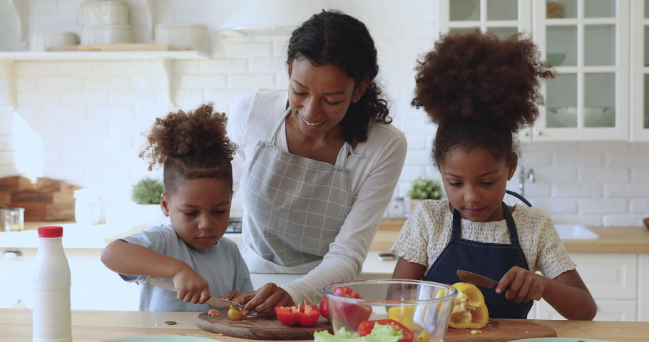 Happy attractive young african american mom in apron teaching little kids siblings cutting fresh vegetables for vegetarian food. Smiling family of three preparing food together at modern kitchen.