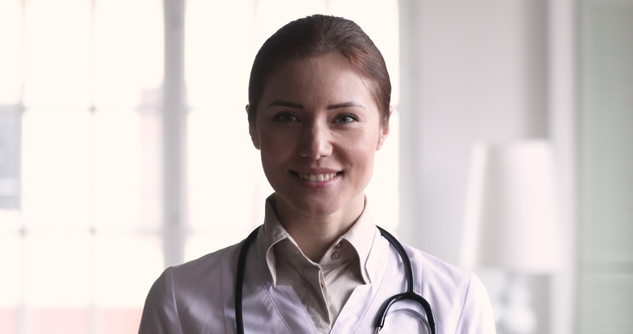 Smiling confident young adult female doctor close up portrait, friendly happy woman physician or nurse professional general practitioner posing with stethoscope looking at camera in medical office