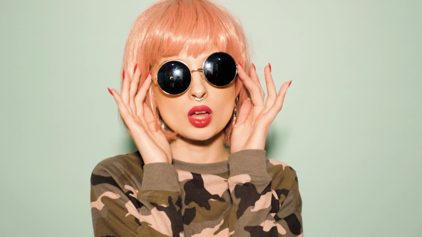 Portrait of young beautiful hipster bad girl in trendy summer clothes and earring in her nose.Sexy carefree smiling woman in studio in pink wig near wall.Positive model dancing in sunglasses