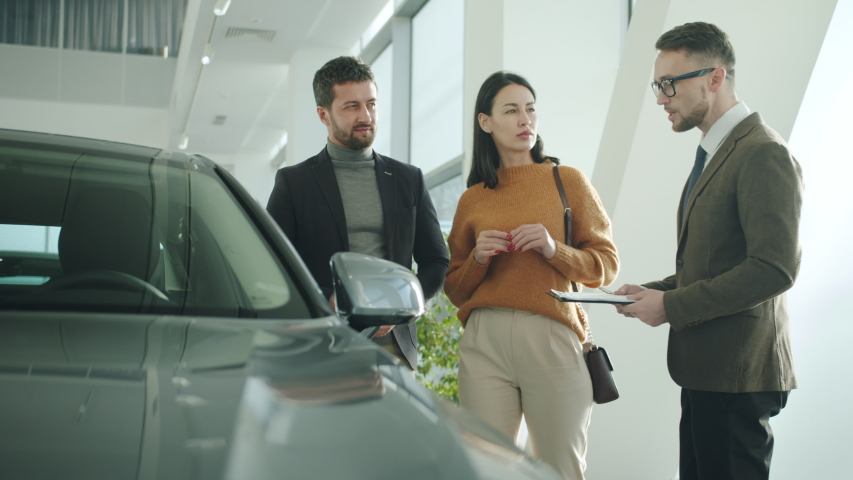 Happy man and woman talking to car dealer in dealership discussing automobiles looking at luxurious new model. Technology and people concept.