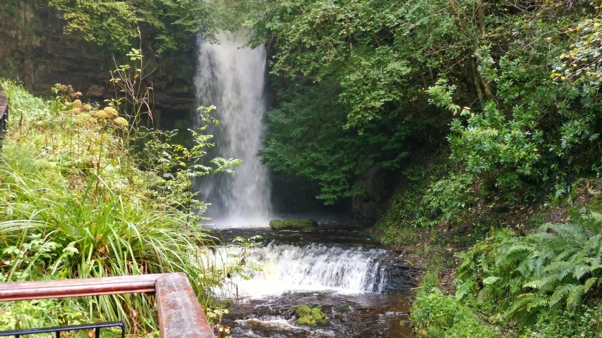 Glencar waterfall nested in small gorge in Ireland and late in Autumn filled with water after rain. | Shutterstock HD Video #1047845446
