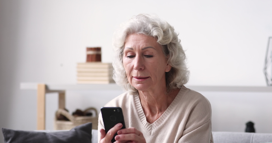 Smiling senior adult grandmother using smartphone sitting on sofa. Happy 70s elder woman holds mobile phone texting message, checking app, reading news at home. Old grandparent learns tech gadget Royalty-Free Stock Footage #1047850693
