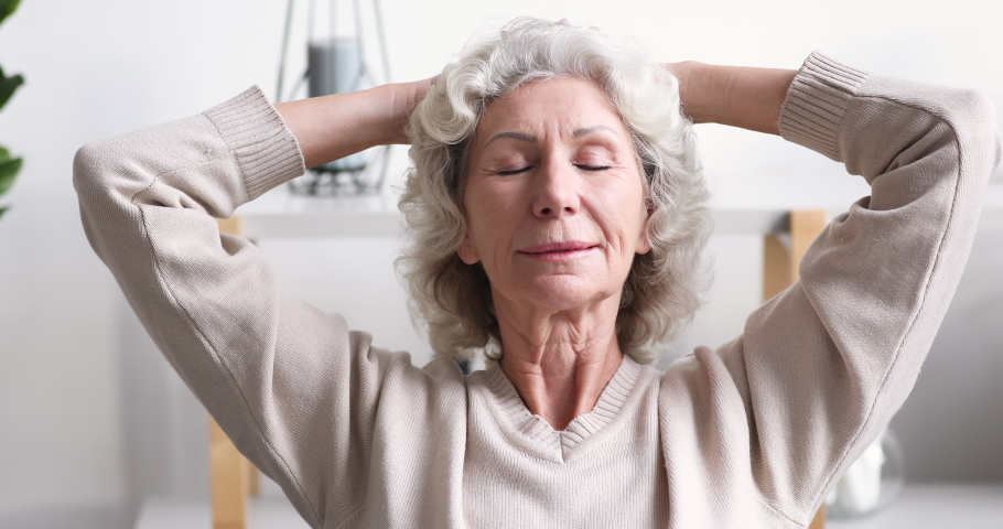 Calm smiling 70 years old woman relaxing at home. Serene senior lady enjoys peace comfort meditating holding hands behind head in living room. Happy granny feels relaxed breathing fresh air concept | Shutterstock HD Video #1047850699