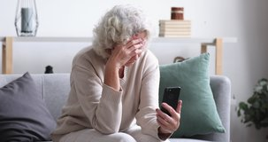 Frustrated senior lady reads bad news in mobile message concept. Sad depressed 70 years old woman looking at smart phone feels shocked. Worried elder female user customer lost money on scam fraud