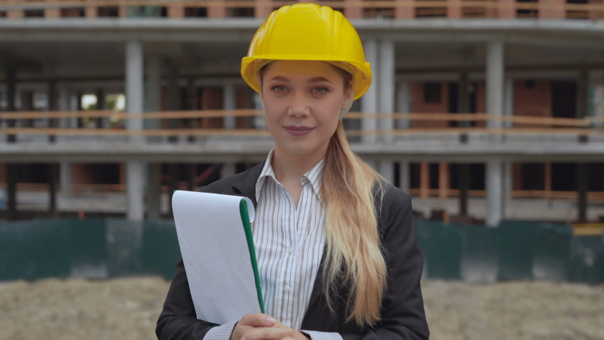 thumbs up . Woman 30 years old engineer in a business suit talking on the phone against the backdrop of a construction site. A woman holds a folder with documents in her hands. 4K Royalty-Free Stock Footage #1047852445