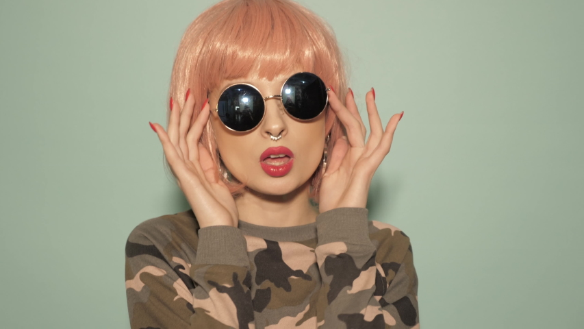 Raw video.young beautiful hipster bad girl in trendy summer clothes and earring in her nose.Sexy carefree smiling woman in studio in pink wig near wall.Positive model dancing in sunglasses
