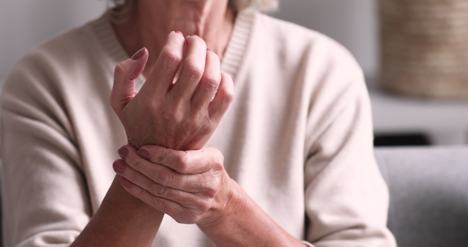 Senior grandmother massaging hand suffering from joint pain. Older woman having rheumatoid arthritis. Elder adult lady touching wrist feeling hurt. Osteoarthritis geriatric disease concept. Close up