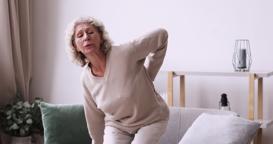 Tired senior woman feels sudden back pain at home. Unhealthy old lady touching spine muscles having lower lumbar ache sitting on sofa. Upset elder grandma suffering from backache. Osteoarthritis
