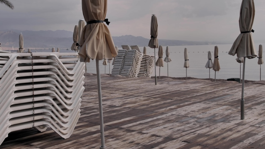 Eilat beach. Medium shot of the empty beach loungers one on another and closed umbrellas of a resort. No tourists on the beach. Quarantine restrictions during Covid-19 pandemic. | Shutterstock HD Video #1047873232