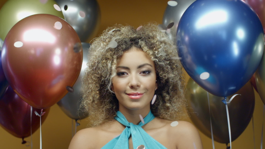 Young curly hispanic woman in turquoise dress dancing on yellow background with multicolored balloons and flying confetti in slow motion. Pretty mixed race girl celebrates holiday at summer party