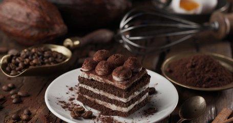 Camera slowly moves over the ingredients for making a tiramisu cake, at the end it focuses on the tiramisu cake itself. 4K video. Blackmagic Cinema 6K.