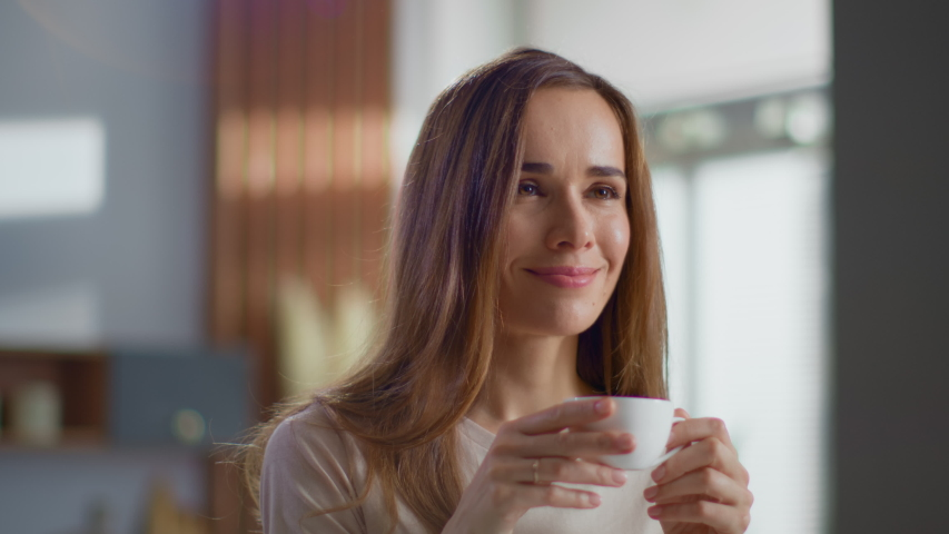 Portrait of satisfied woman drinking tea on kitchen. Attractive lady enjoying cup of coffee at home in slow motion. Smiling woman holding cup of tea in hands at morning