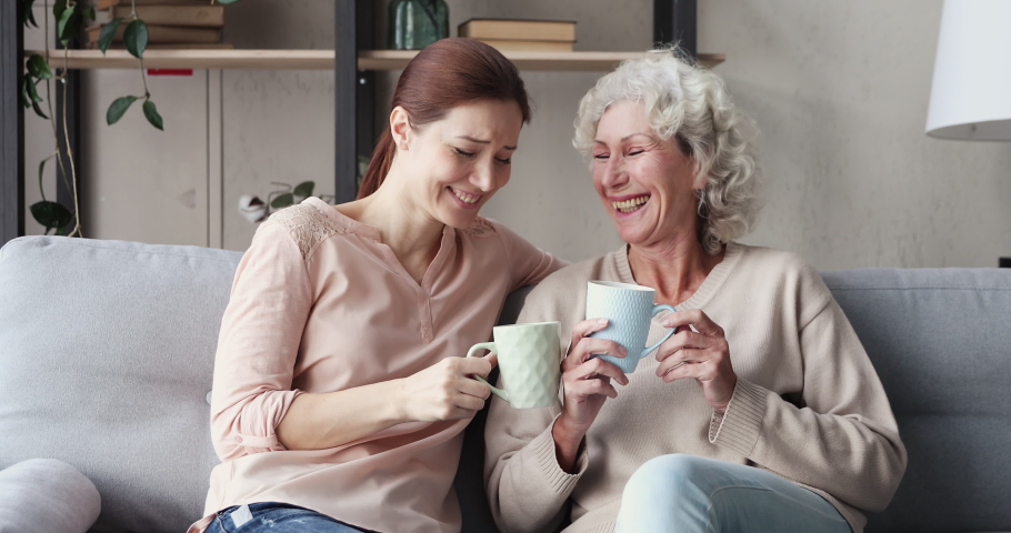 Happy 2 two age generations women family chatting drinking tea at home. Relaxed old elder mother and young adult daughter talking and laughing sitting on sofa, resting in cozy living room together.