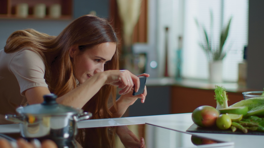 Portrait of food blogger taking picture on mobile phone of fruits on kitchen table. Attractive woman using smartphone indoor in slow motion. Young lady making fod photo at domestic kitchen Royalty-Free Stock Footage #1047905377