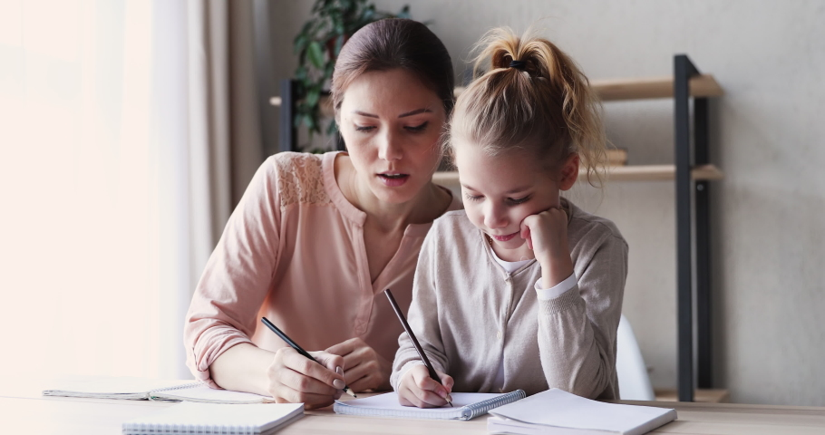 Cute small 6-7 years kid daughter learning writing with young mom tutor. Adult parent mother teaching school child girl helps with homework studying sitting at home table. Children education concept