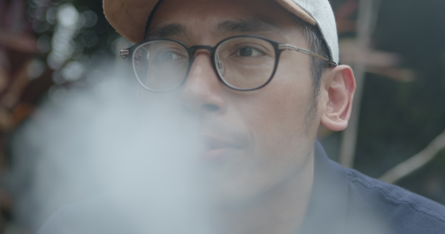 Asian man smoking inhaling and exhaling vape | Shutterstock HD Video #1047913858