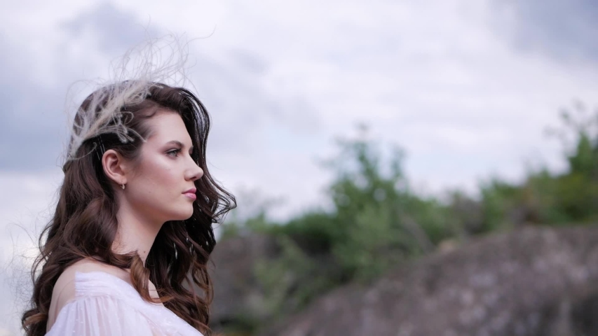 Close up side portrait of pretty brunette girl in a white dress posing outdoors enjoying summer. Woman looking to evening sky in countryside.   Shutterstock HD Video #1047916906