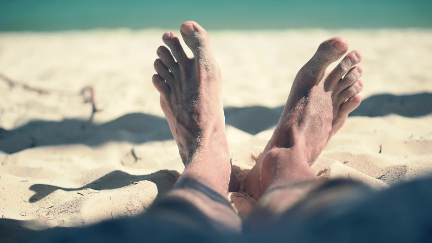 Man Lying On Beach And Moving Legs On Holiday Vacation.Tan Guy Relaxing Sandy Beach In Sunbed On Caribbean Exotic Resort.Legs Man On Beach Sun Lounger Sandy Shore Sunbathing.Happy Healthy Tourist Rest Royalty-Free Stock Footage #1047923326